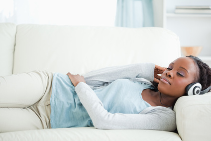 Young woman listening to music while lying on couch